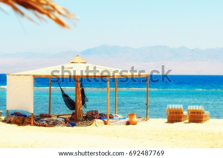 Sunbeds, hammock & simple tent at sandy beach by the seaside. Red Sea in Egypt (Nuweiba bedouin village). Bright summer sunny colors. Tranquil & chilling out day. #692487769