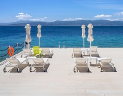 Sunbeds on a sunny day on the beach at the Greek spa resort with the hot springs of Loutra-Edipsou on the island of Evia (Euboea) in the Aegean Sea