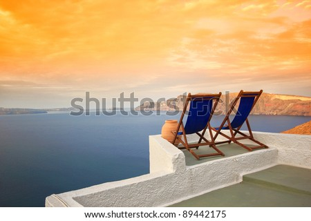 Sunbeds on Santorini's roofs at sunrise