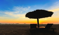 Sunbeds sun loungers umbrellas under palm trees White sandy beaches sea views with horizon, colorful night sky calm Beautiful sunset scenery Silhouette style