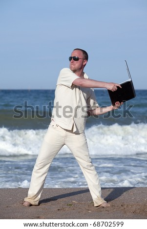 Sunburned businessman at the beach throwing his laptop. Concept of protesting against work on vacation