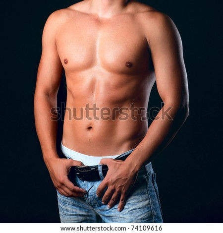 Sunburnt muscular male torso in the jeans