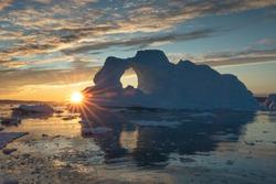 Sunburst behind a massive iceberg with a hole in it during the midnight sun season. Disko bay, Greenland.