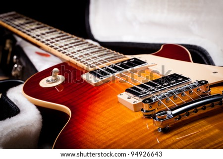 Sunburst Electric Guitar Laying in a Hard Shell Electric Guitar Case