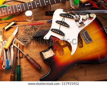 Sunburst electric guitar on guitar repair desk or in a repair work shop. Neck and pickguard detached. Double cutaway solid body guitar. Shallow depth of field.