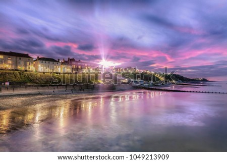 Sunburst over Cromer town - As dusk appears, the soft lights of streets and buildings come on. Cromer has one of the best, and flourishing, piers in England and the only surviving end of pier show in  #1049213909