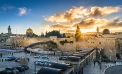 Sunburst through the clouds over the Temple Mount with Dome of the Rock and Al Aqsa mosque, and Western Wall plaza entrance, with Jewish worshippers wearing masks due to COVID-19 guidelines in Israel