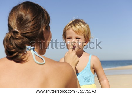 Suncare on the beach: Mother applying sunscream to her daughter