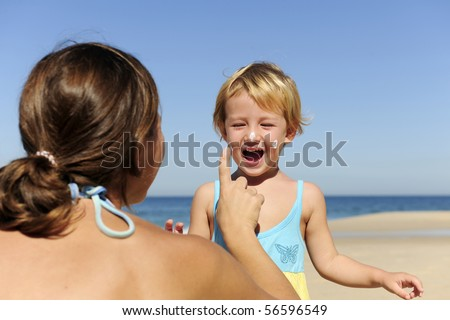 Suncare on the beach: Mother applying sunscream to her happy child - stock photo
