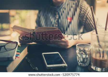 Sunday morning lifestyle scene of young hipster asian woman reading book in cafe with. Weekend activity or hobby concept with vintage filter effect