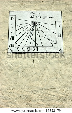 Sundial on a old swiss church showing nearly 11 O\'clock, whereas summertime is actually nearly midday.  Inscription reads \'Everything to the glory of God\'.
