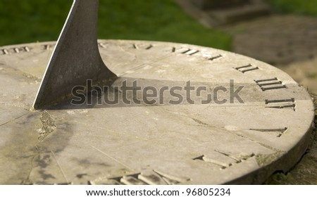 Sundial on sunny day shows time at edge of shadow