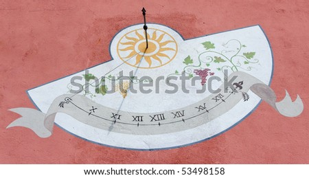 Sundial painted on house wall in Italy