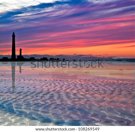 Sundown and lighthouse silhouettes on the beach at Plouguerneau in France