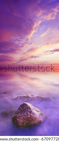 Sundown on sea with bright color on the sky and stone on foregrounds. Vertical panorama