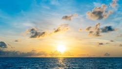 Sundown over the sea on the beach summer morning background.  The sun between amazing clouds. Vietnam natural sundown landscape on the beach.