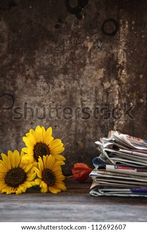 Sunflower and a stack of newspaper, autumn still life on the old wooden table.