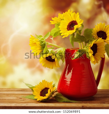 Sunflower bouquet in red jug on wooden table over beautiful autumn bokeh background