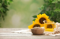 Sunflower oil and seeds on wooden table against blurred background, space for text