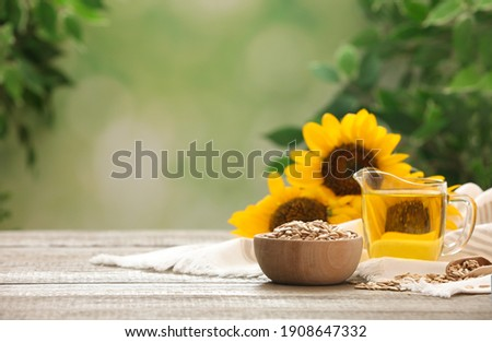 Sunflower oil and seeds on wooden table against blurred background, space for text Foto stock ©