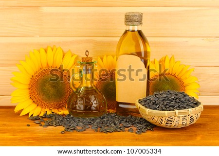 sunflower oil and sunflower on wood background