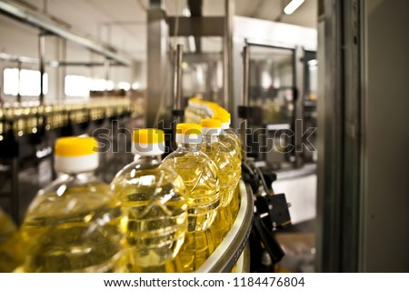 Sunflower oil in the bottle moving on production line. Shallow dof. stock photo