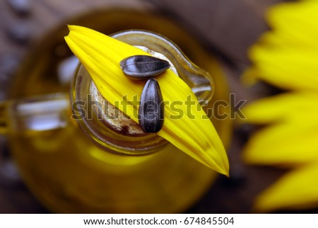 Sunflower, seeds and a bottle of oil on a dark wooden background. #674845504