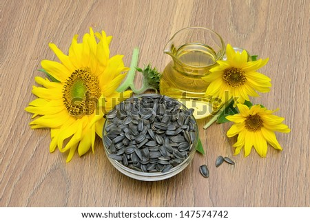 sunflower seeds and flowers, sunflower oil on board. top view - horizontal photo.