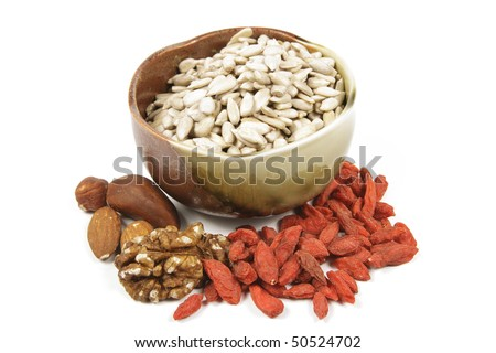 Sunflower seeds in a brown and green bowl with mixed nuts and goji berries on a reflective white background