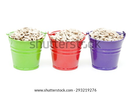 Sunflower seeds in bucket, isolated on white background