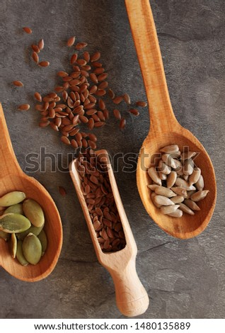 Sunflower seeds, pumpkin seeds and flax seeds on the wooden spoons.