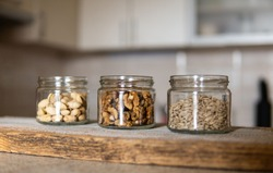 Sunflower seeds, walnut and pistachio in a jars which standing on a white vintage table with a kitchen on background. Nuts is a healthy vegetarian protein and nutritious food. Nuts on rustic old wood.