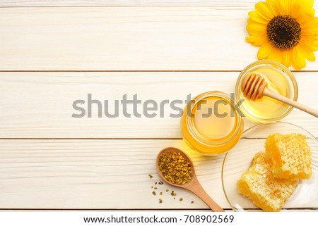 Sunflower with honey, Honeycomb and honey dipper on light wooden table. Top view with copy space