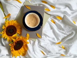 Sunflowers, coffee cup and books on the bed shot from above Top view, flat lay, copy space. Summer background. Relaxing at home concept.