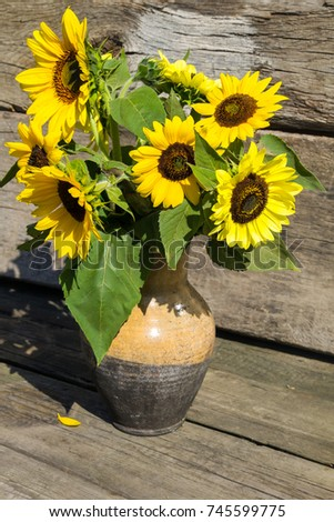 Sunflowers In Vintage Clay Jug On Wooden Background 745599775