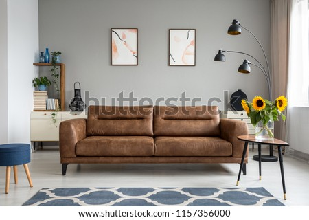 Sunflowers on wooden table next to leather sofa in living room interior with posters. Real photo