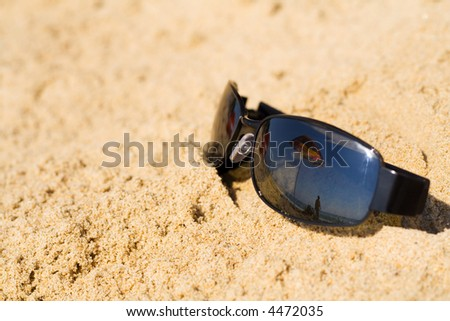 Sunglass in the sand reflecting beach umbrella and summer sky - lots of copy space