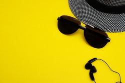 Sunglasses, a man's hat and headphones. Summer and staycation concept, creative layout on a yellow background, top view, copy space