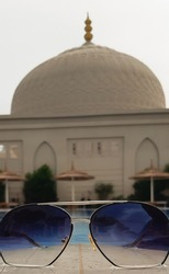 Sunglasses against the background of a muslim mosque and a swimming pool with umbrellas for shade in an eastern country resort