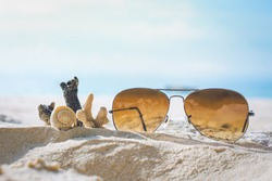 Sunglasses and Coral on the sand.