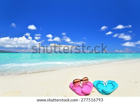 Sunglasses and slippers at tropical beach -- Tropical beach vacation and travel concept