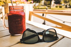 Sunglasses and smoothies on the table on a sunny day