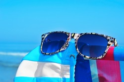 sunglasses and swimsuit on a colorful deckchair on the beach