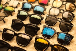 Sunglasses apparel in market shop with big discounts on eyewear and a huge sale.  Blurred edges with focus on blue glasses for outdoors.