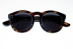 Sunglasses, black and dark brown frames and light stripes, White background.
