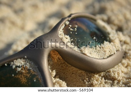 Sunglasses buried in white tropical sand