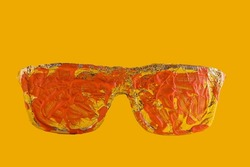 Sunglasses covered with aluminum foil. Pink acrylic paint on glass. Isolated on yellow.