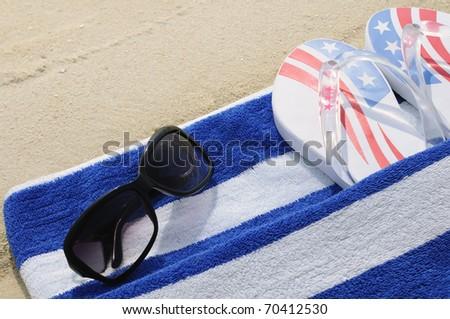 Sunglasses, flip flops and beach towel on the sand.
