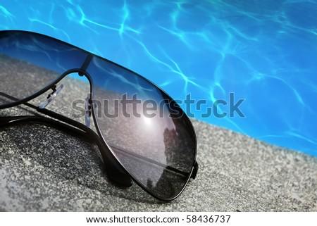 Sunglasses  next to a pool