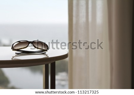 Sunglasses on a table in a luxury hotel room or apartment with blurred view of the ocean behind